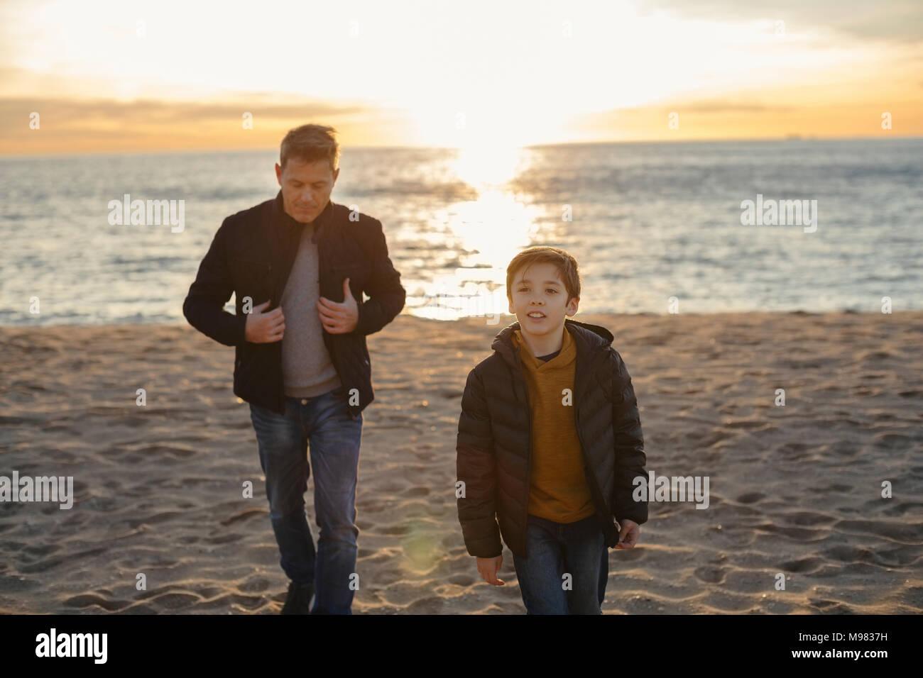 Père et fils marche sur la plage au coucher du soleil Photo Stock