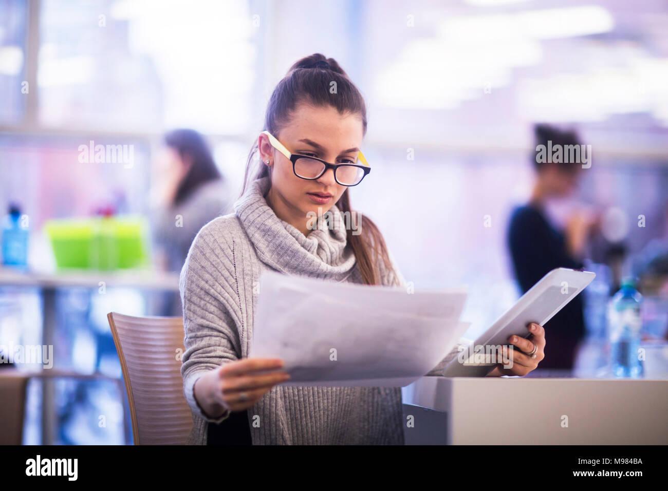 Portrait de jeune femme travaillant dans un bureau Photo Stock
