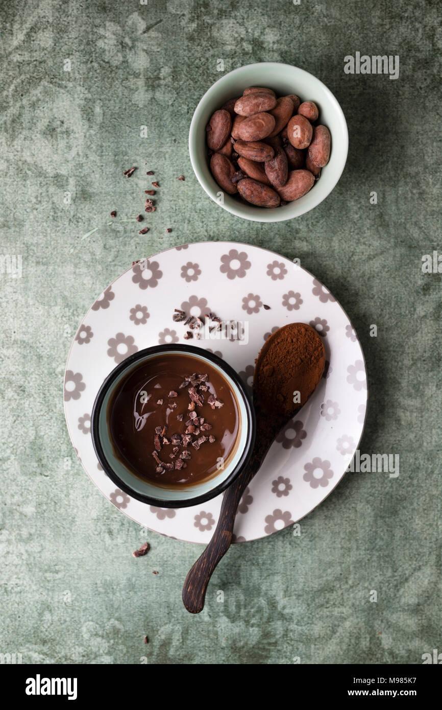 Tasse de chocolat au lait avec le cacao, cacao nibs et les fèves de cacao Photo Stock