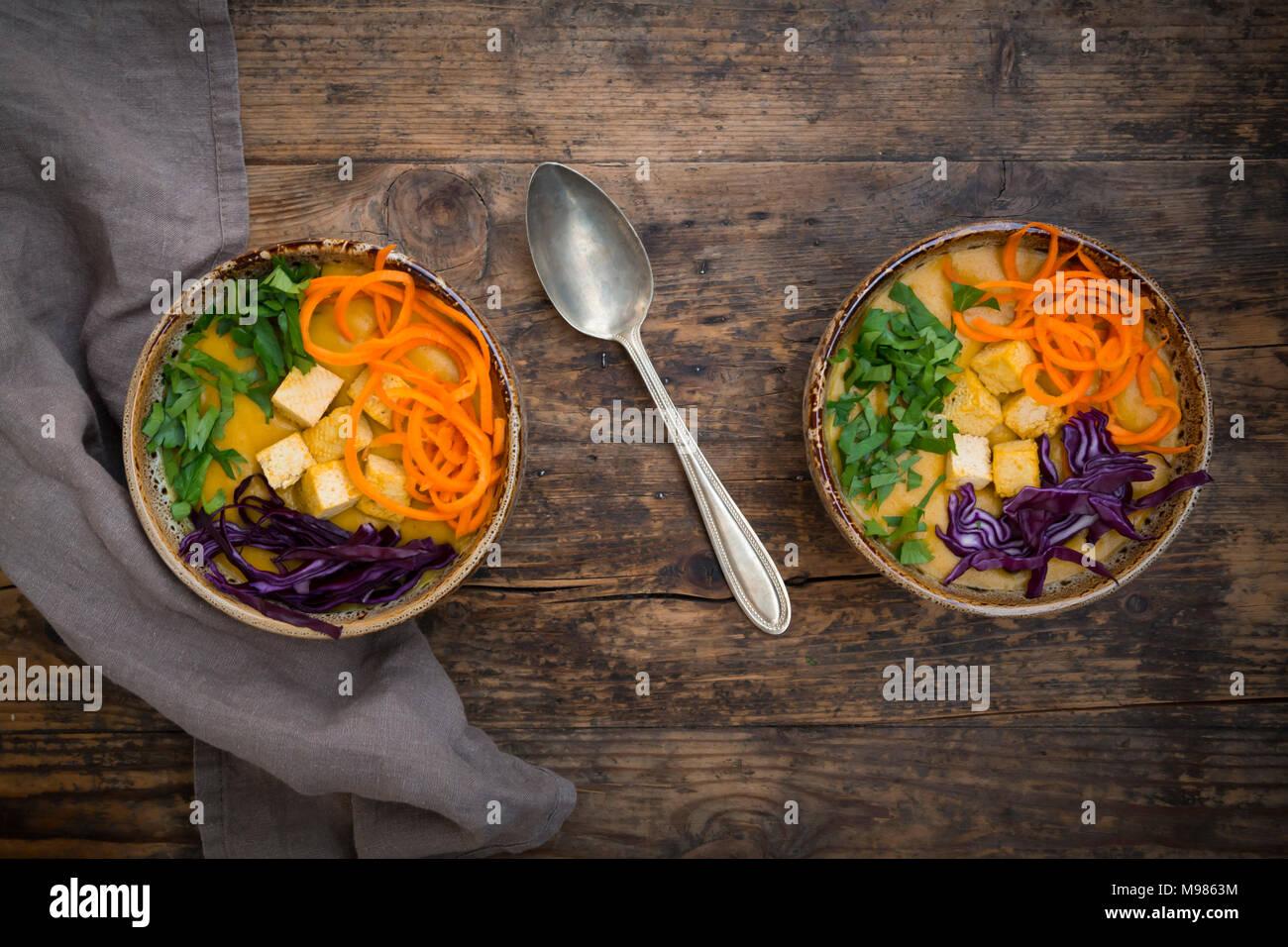 Le curcuma curry plat avec les carottes, le tofu, le chou rouge et le persil dans un bol Banque D'Images