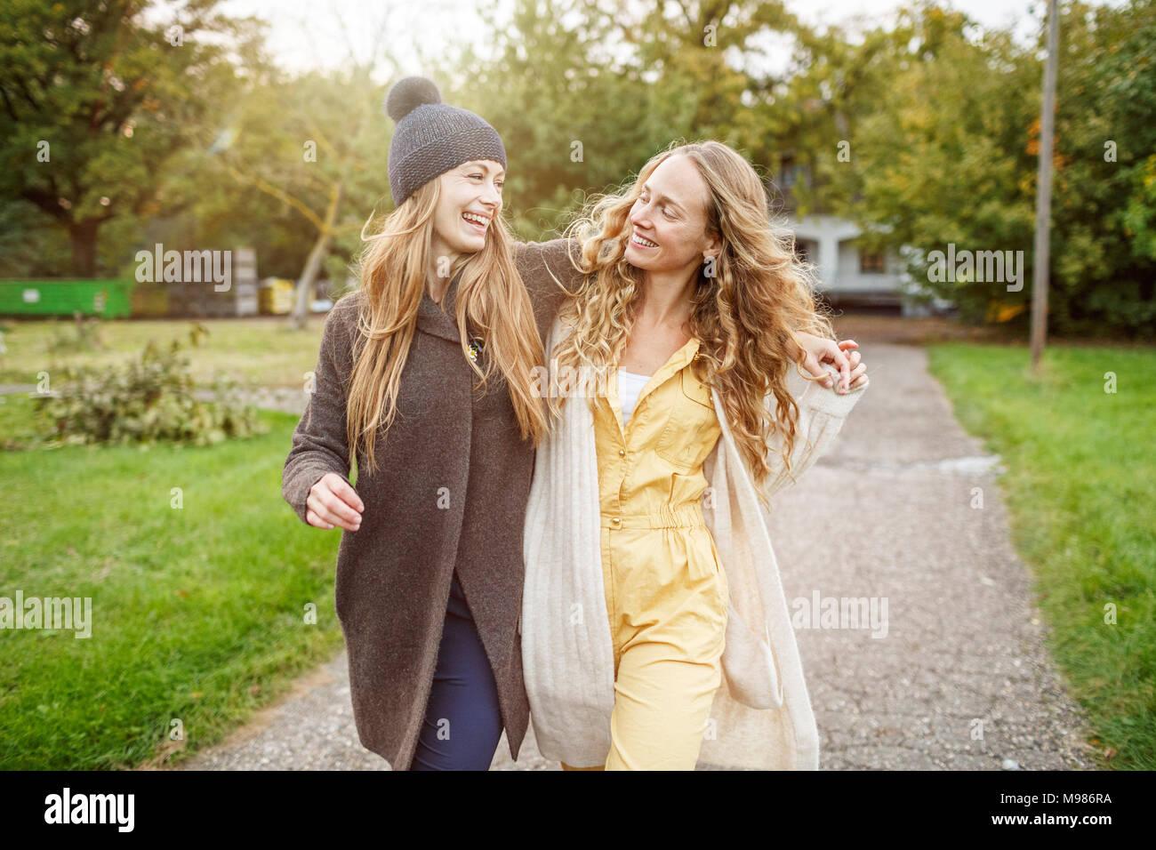 Deux femmes marchant heureux in rural landscape Photo Stock