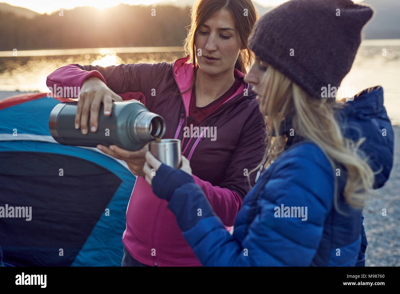 Deux femmes avec boisson chaude du camping au lac Banque D'Images