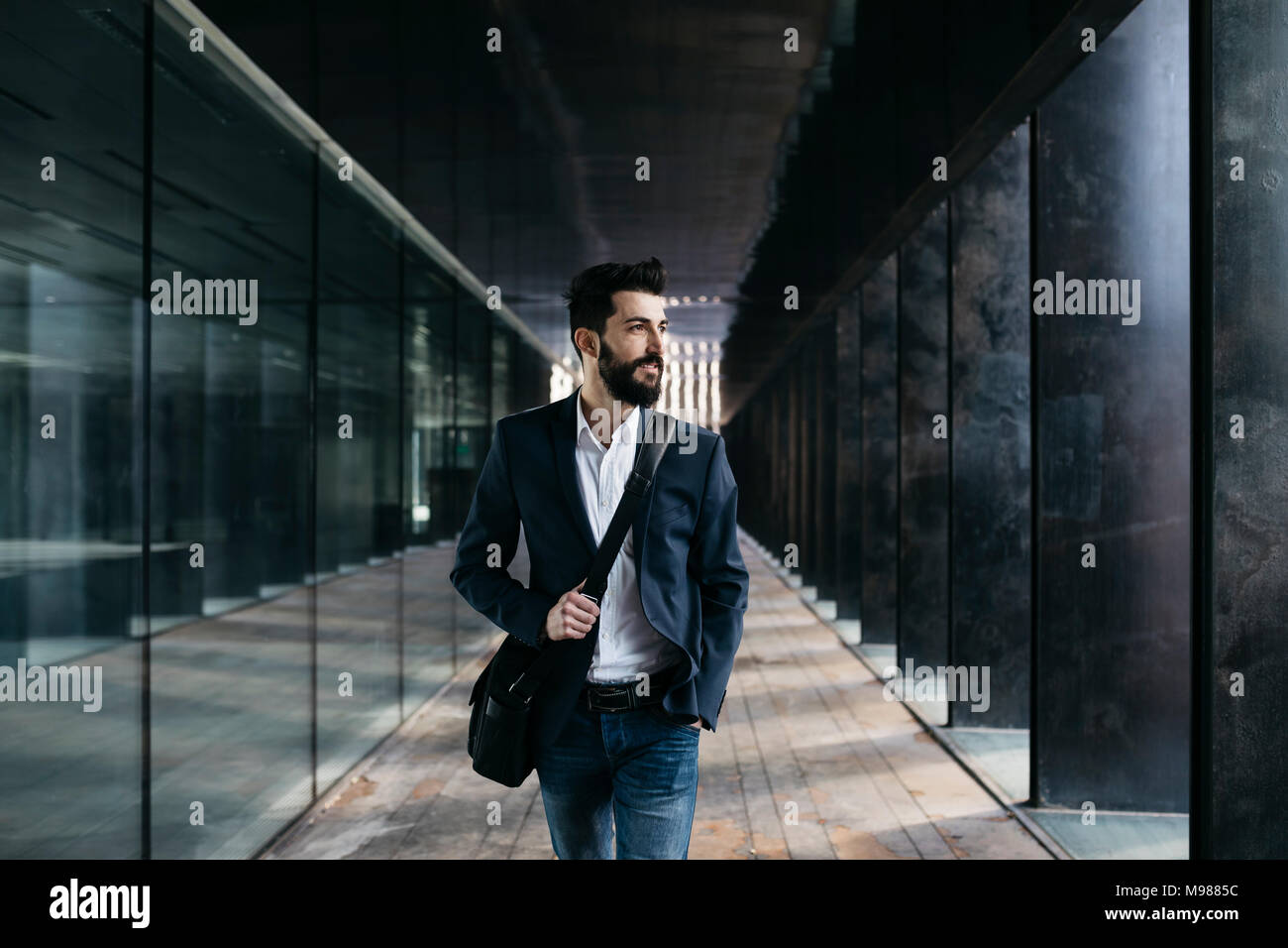 Businessman walking le long d'arcade Photo Stock