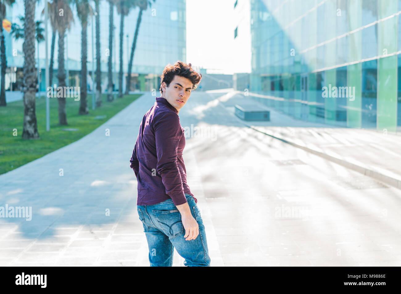 Jeune homme sérieux marcher dans la ville se retourner Photo Stock