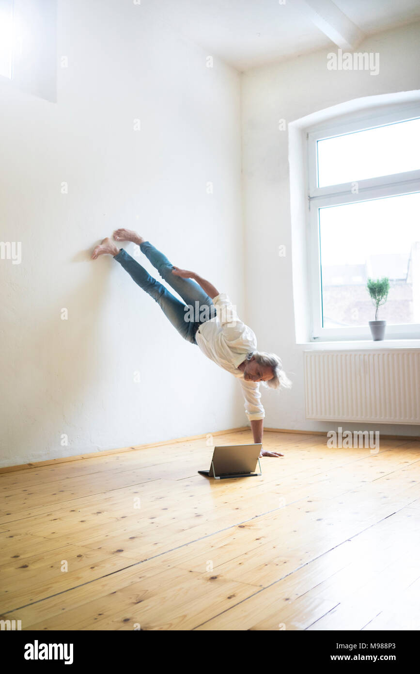 Man doing a handstand in empty room looking at tablet Photo Stock