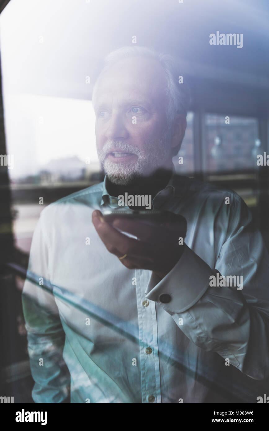 Portrait of mature businessman à la fenêtre using cell phone Banque D'Images