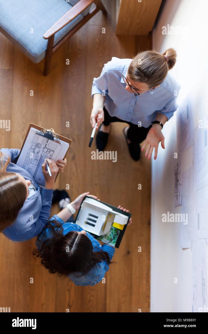 Groupe de femmes architectes ayant une réunion, vu de directement au-dessus Photo Stock