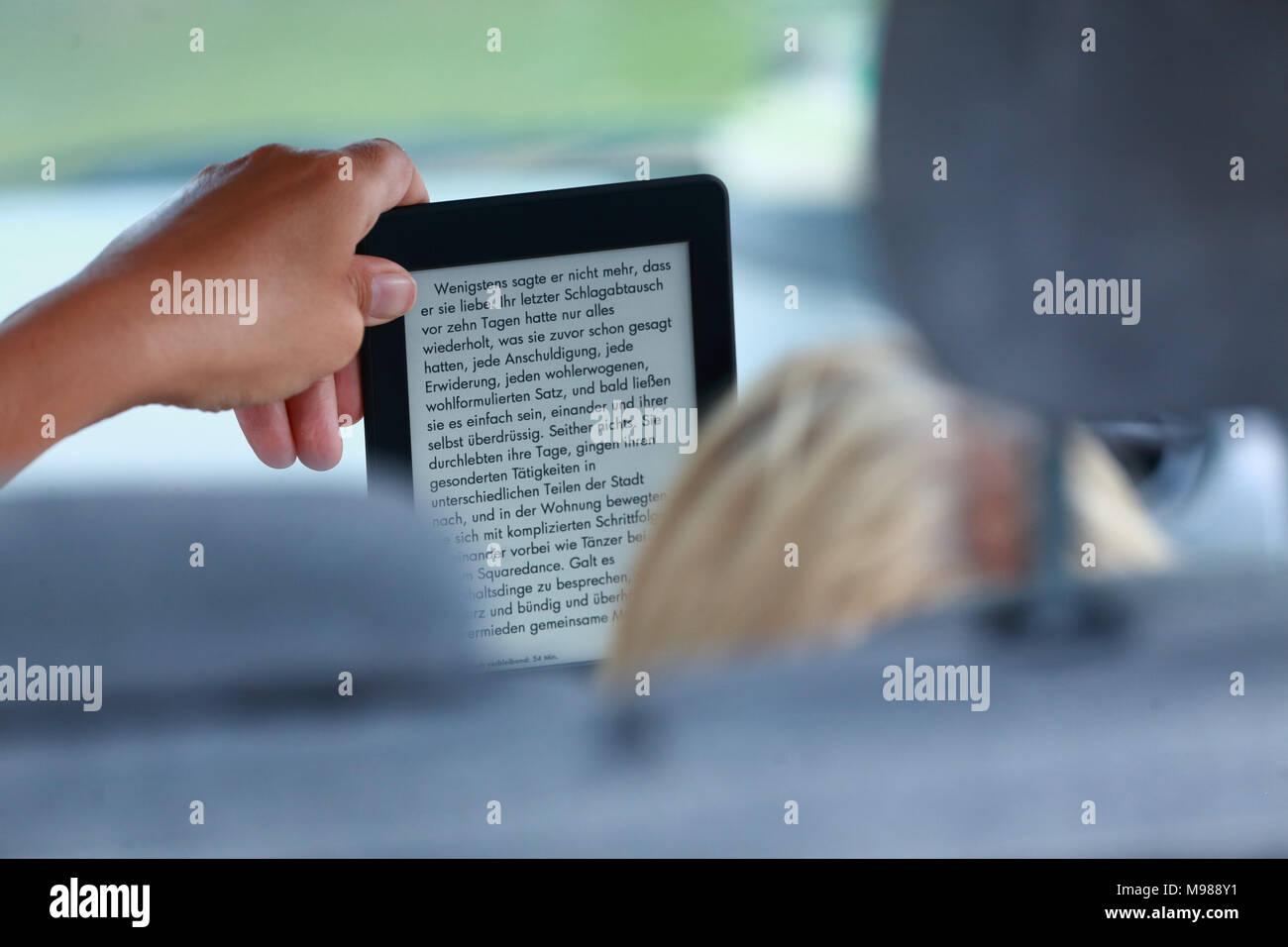 Blonde womand de derrière assis sur le siège passager dans une voiture de la lecture d'un livre allemand sur un e-reader Photo Stock
