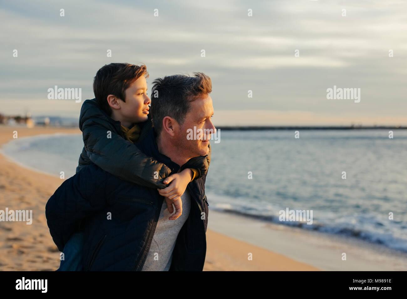 Father carrying son piggyback sur la plage Photo Stock