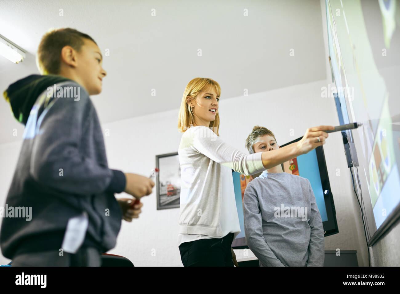 Avec les élèves de l'enseignant en classe au tableau blanc interactif Photo Stock