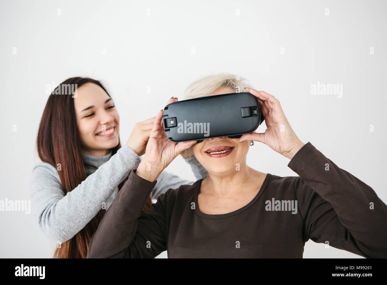 Une jeune fille explique à une femme âgée comment utiliser des lunettes de réalité virtuelle. L'ancienne génération et les nouvelles technologies. Photo Stock