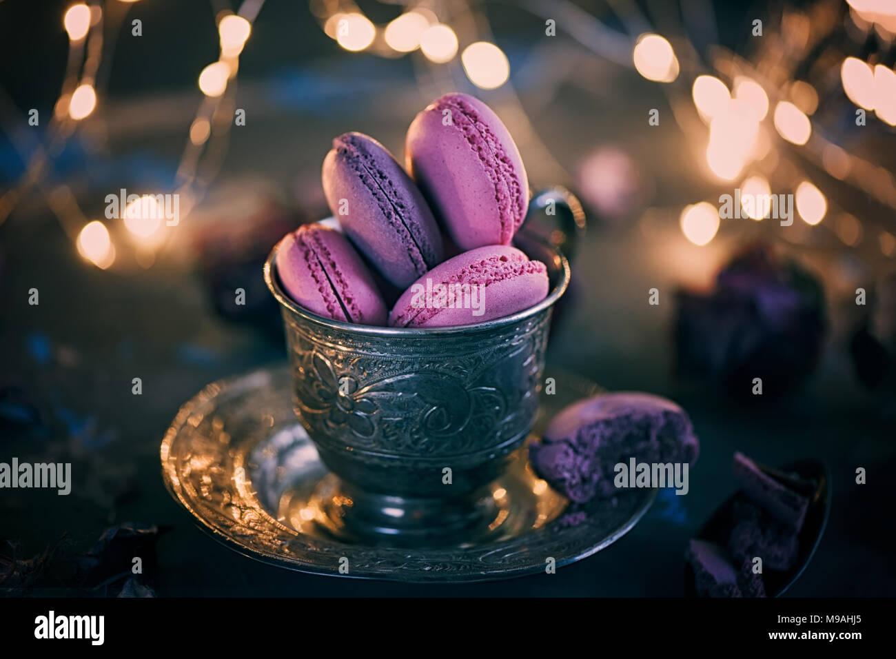 Des petits macarons sur une coupe de métal de l'argent avec de l'effet bokeh voyants sur le fond en bois. Focus sélectif. Spase copie Photo Stock