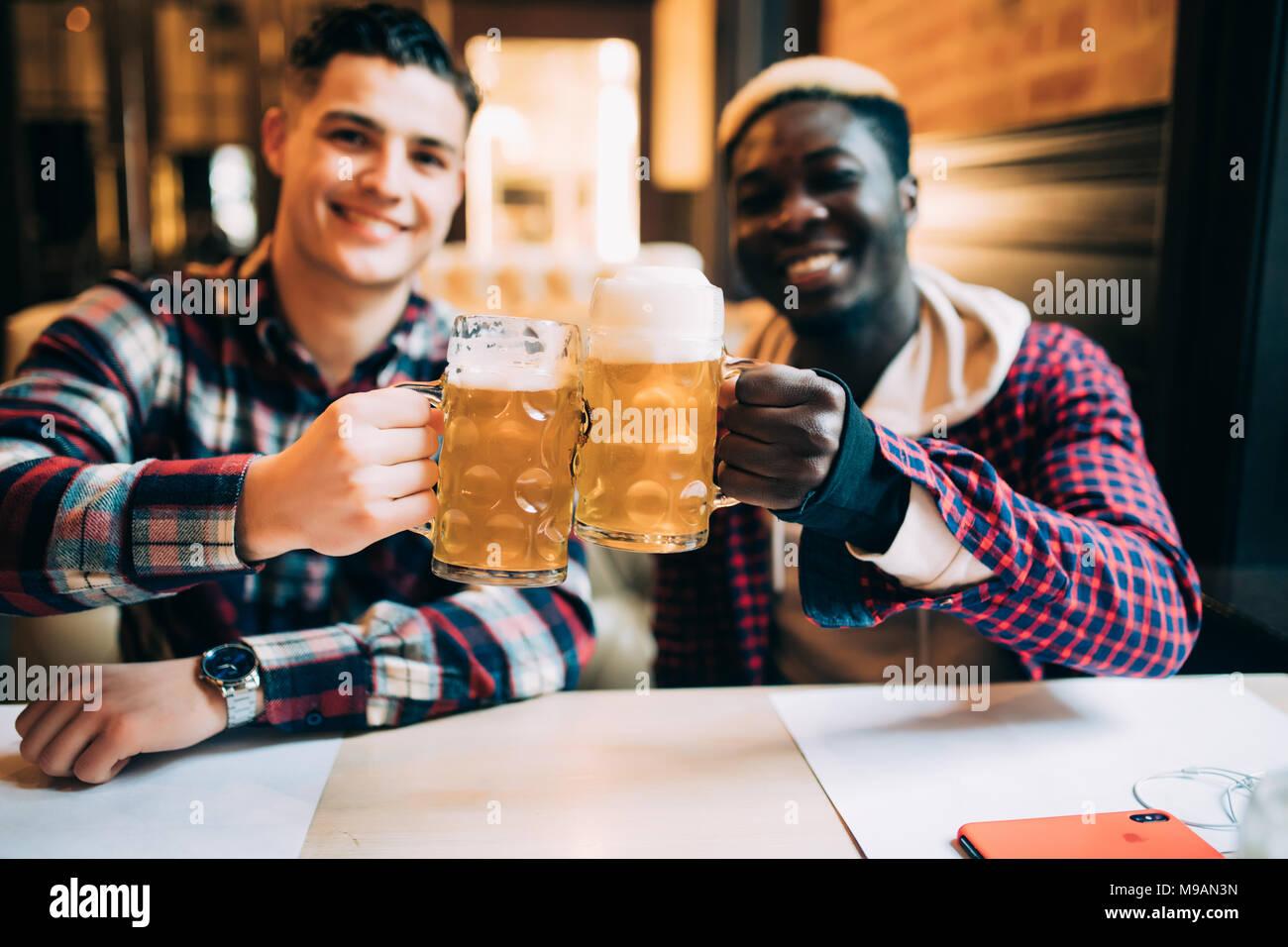 Deux meilleurs amis ou camarades de collège ayant la bière dans un pub. Homme African parle à son ami de race blanche, looking at camera Photo Stock