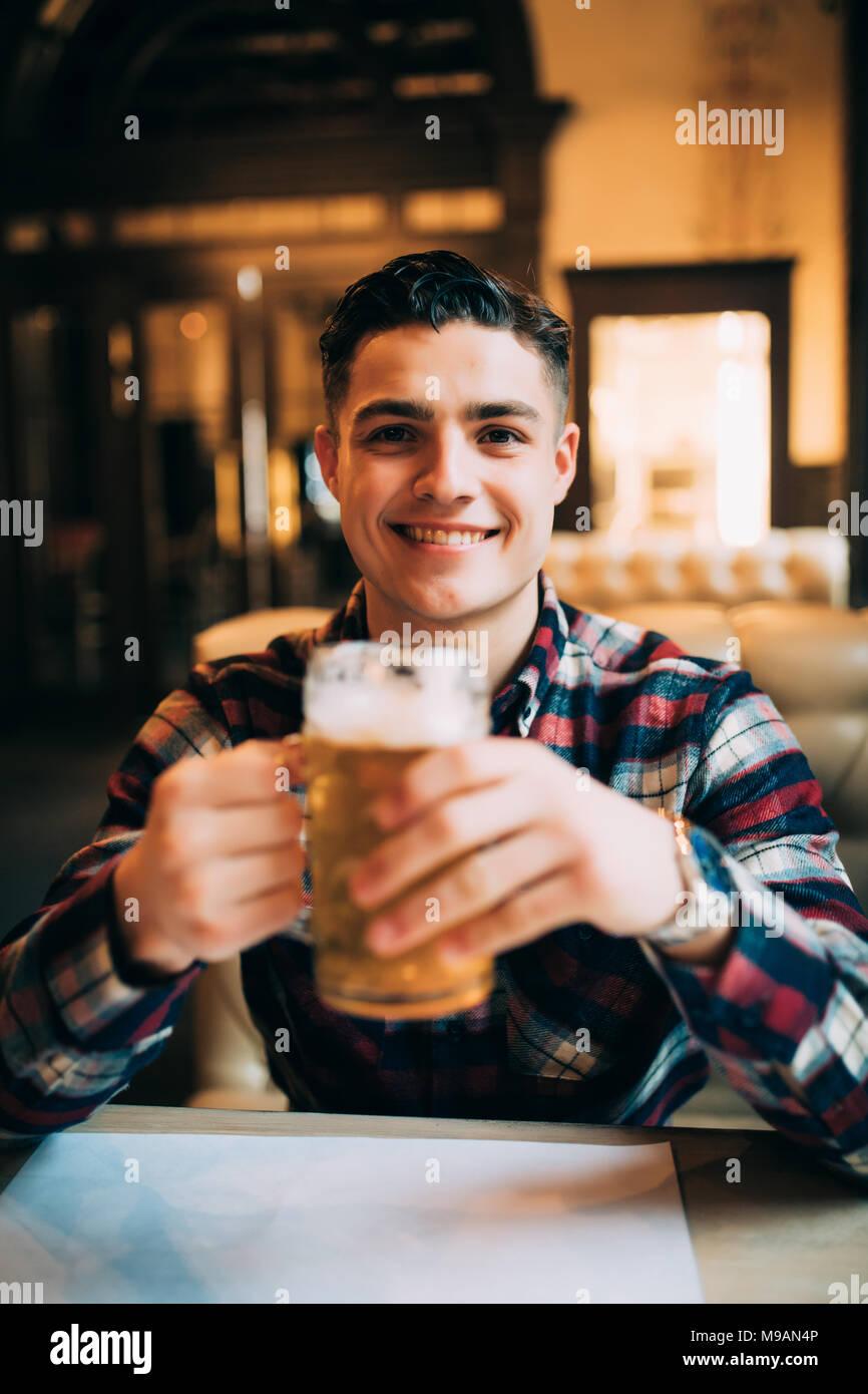 Un jeune homme avec une bière dans un bar Photo Stock