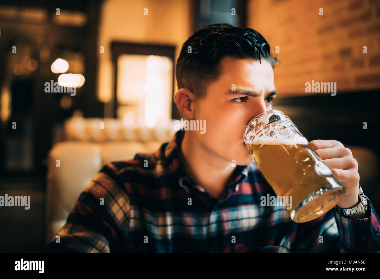 Man drinking beer. Young man drinking beer assis à l'comptoir bar Photo Stock