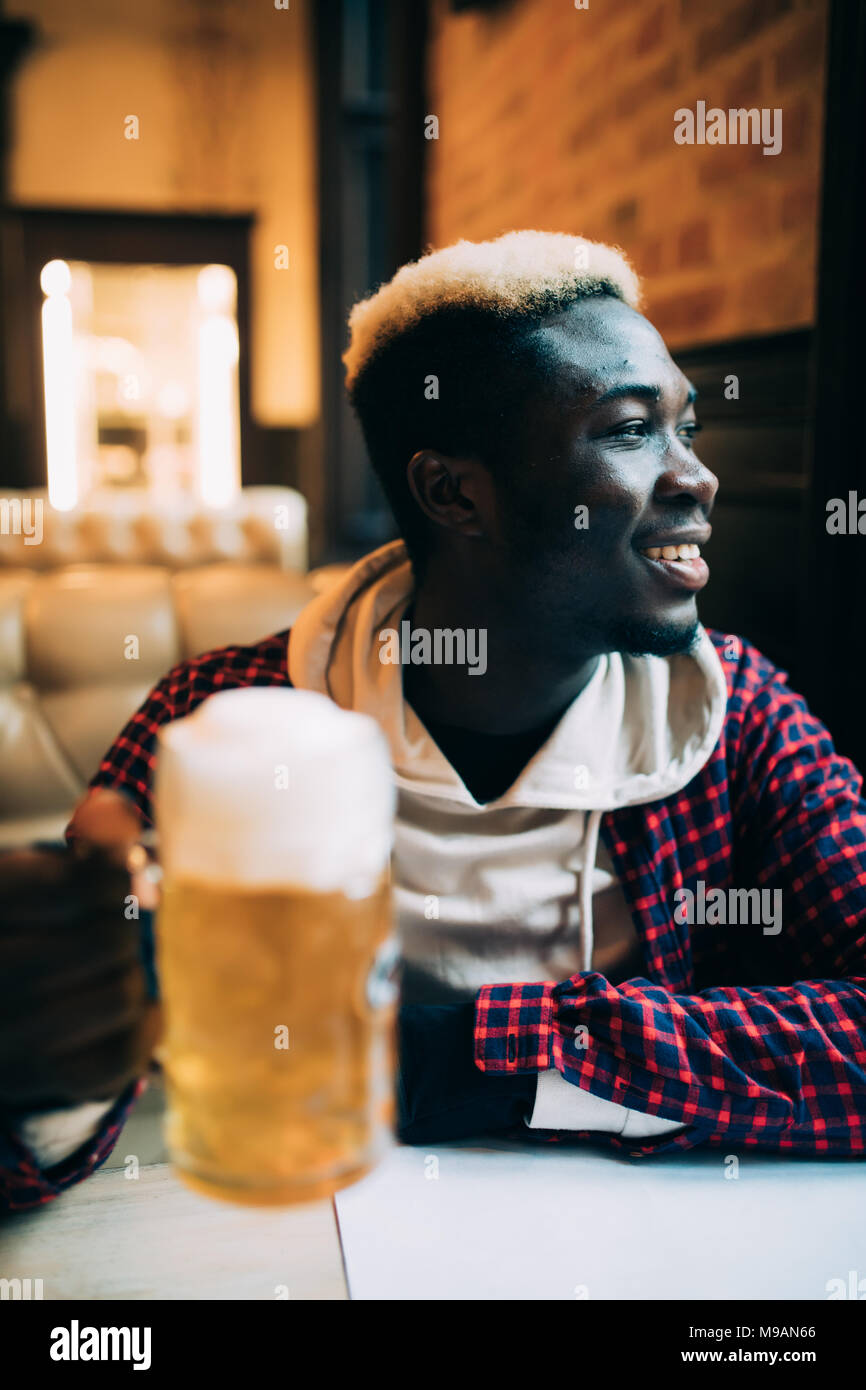 Happy handsome african american young man drinking beer Photo Stock