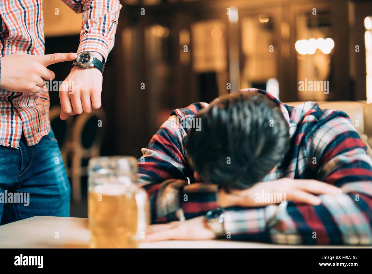 Jeune homme dans des vêtements décontractés est en train de dormir près de la chope de bière sur une table dans un pub, un autre homme est le réveiller. Photo Stock