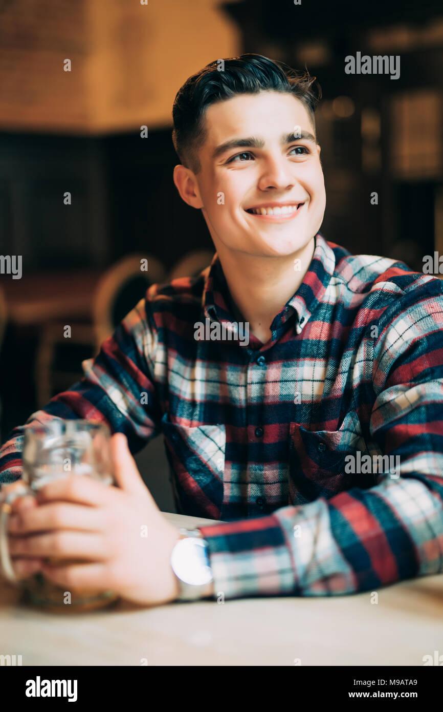 Jeune homme assis au comptoir du bar avec une pinte de bière légère Photo Stock