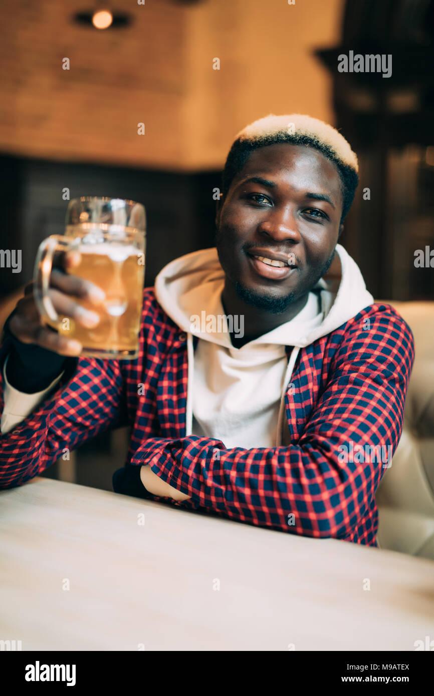 African American man avec verre au bar Photo Stock