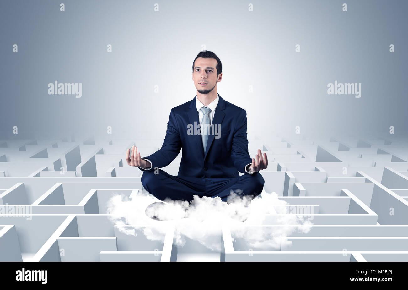 Young businessman méditer en position de yoga sur un nuage avec l'infini maze concept Photo Stock