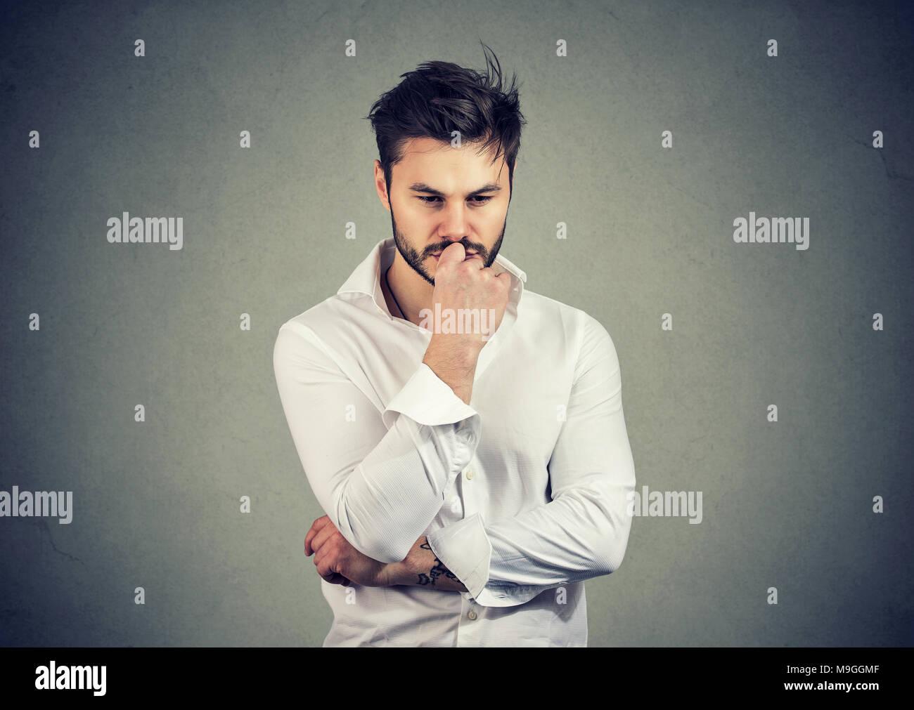 Jeune homme sérieux touchant les lèvres et l'air inquiet tout en résolvant grande question à l'esprit. Photo Stock