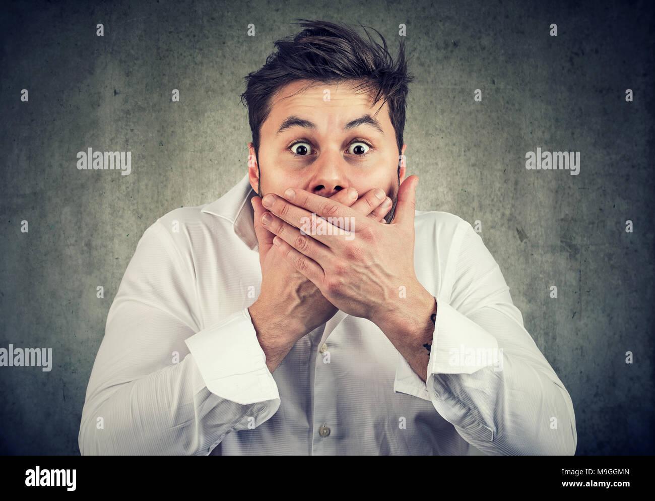 Jeune homme choqué en chemise blanche couvrant la bouche maintenant crier tout en regardant avec étonnement face à l'expression. Photo Stock