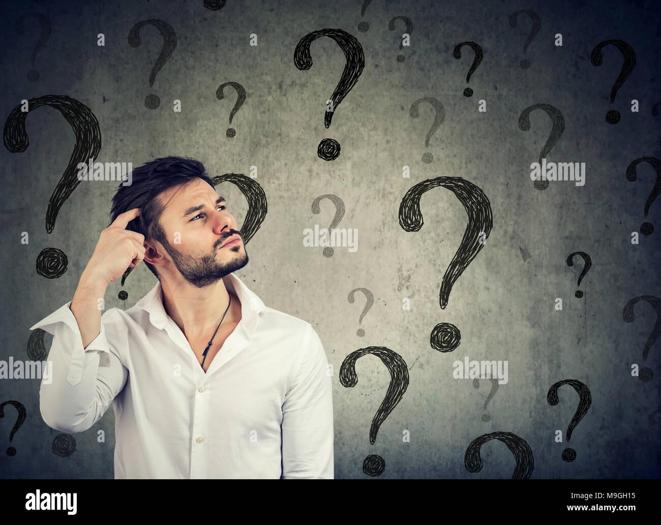 Bel homme confus réfléchie a trop de questions et pas de réponse Photo Stock