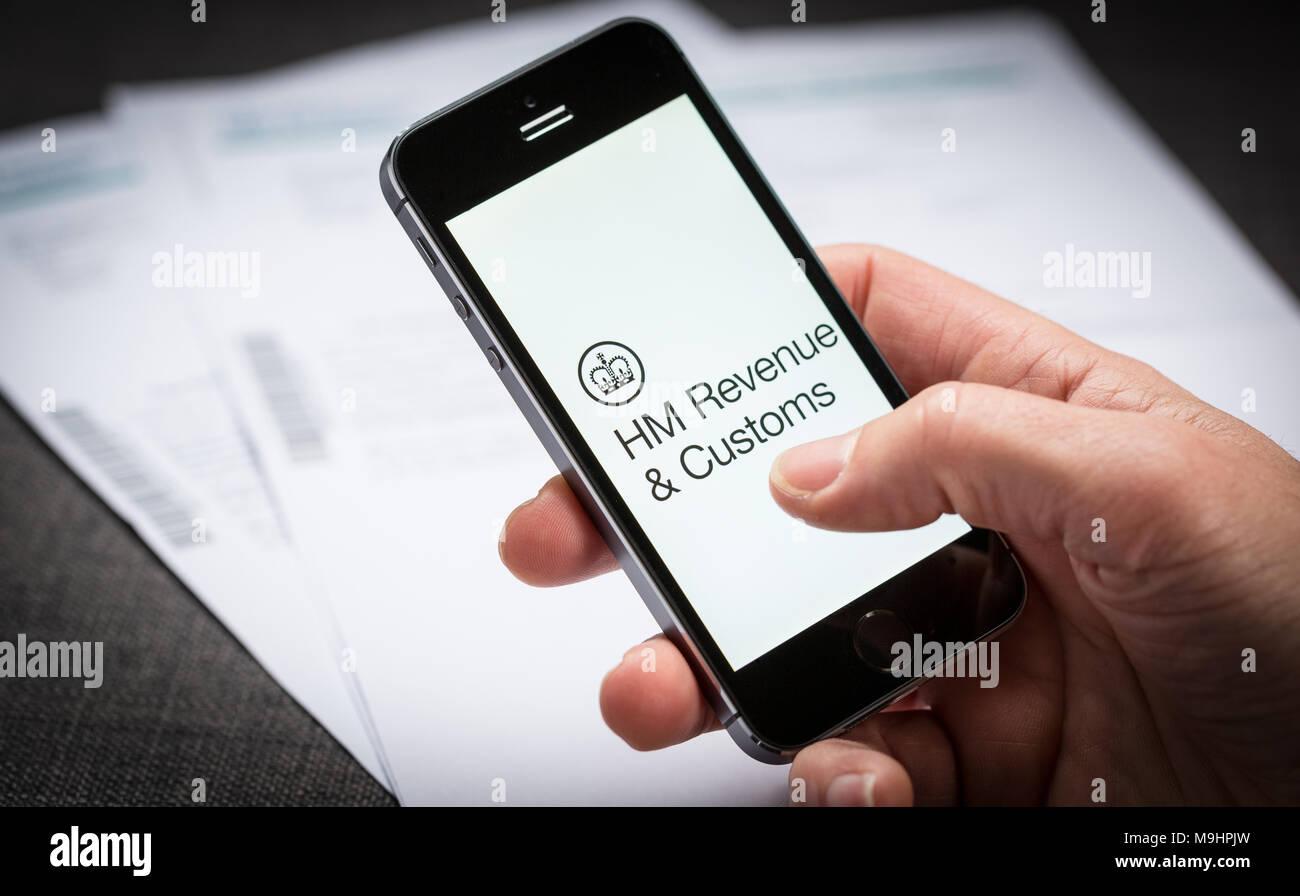 Un homme en utilisant le HMRC HM Revenue and Customs app sur un iPhone au Royaume-Uni Photo Stock