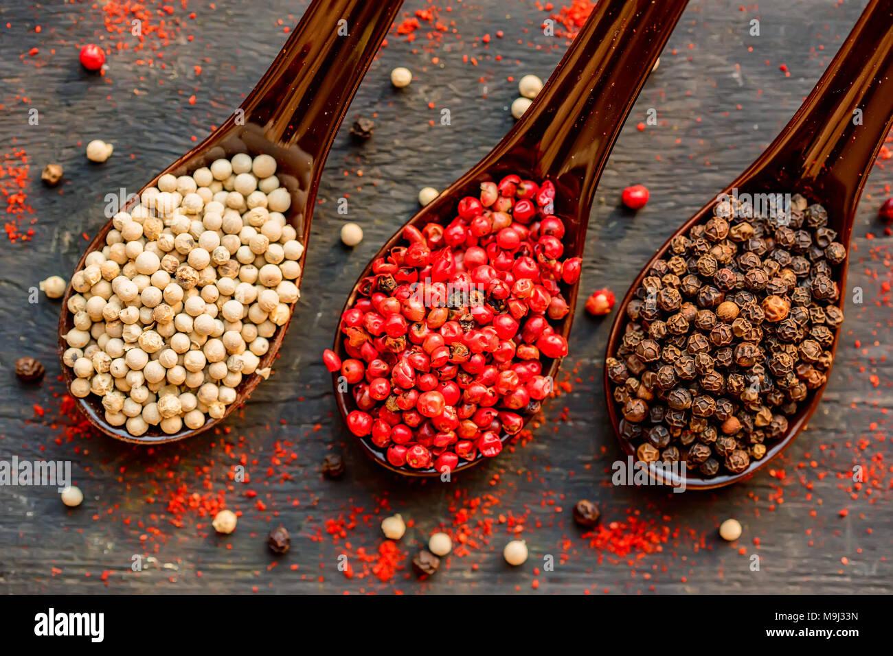 Trois cuillères de noir, poivre rose et blanc Photo Stock