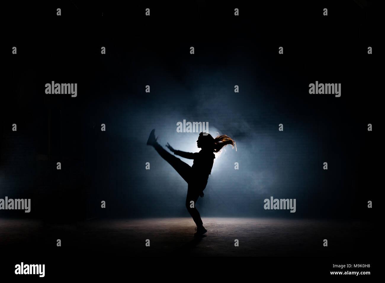 Jeune danseuse aux cheveux longs levant sa jambe sur scène sombre. souple fille. dancing se déplace.jambes étendues Banque D'Images