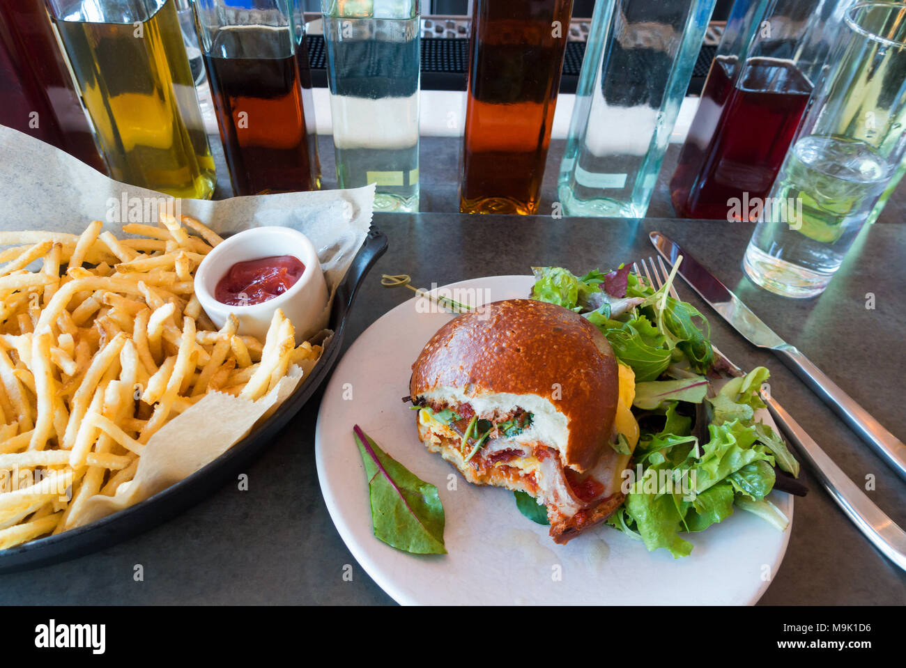 Sandwich œuf et bacon grillé sur un rouleau avec mélange de salade de légumes verts Photo Stock