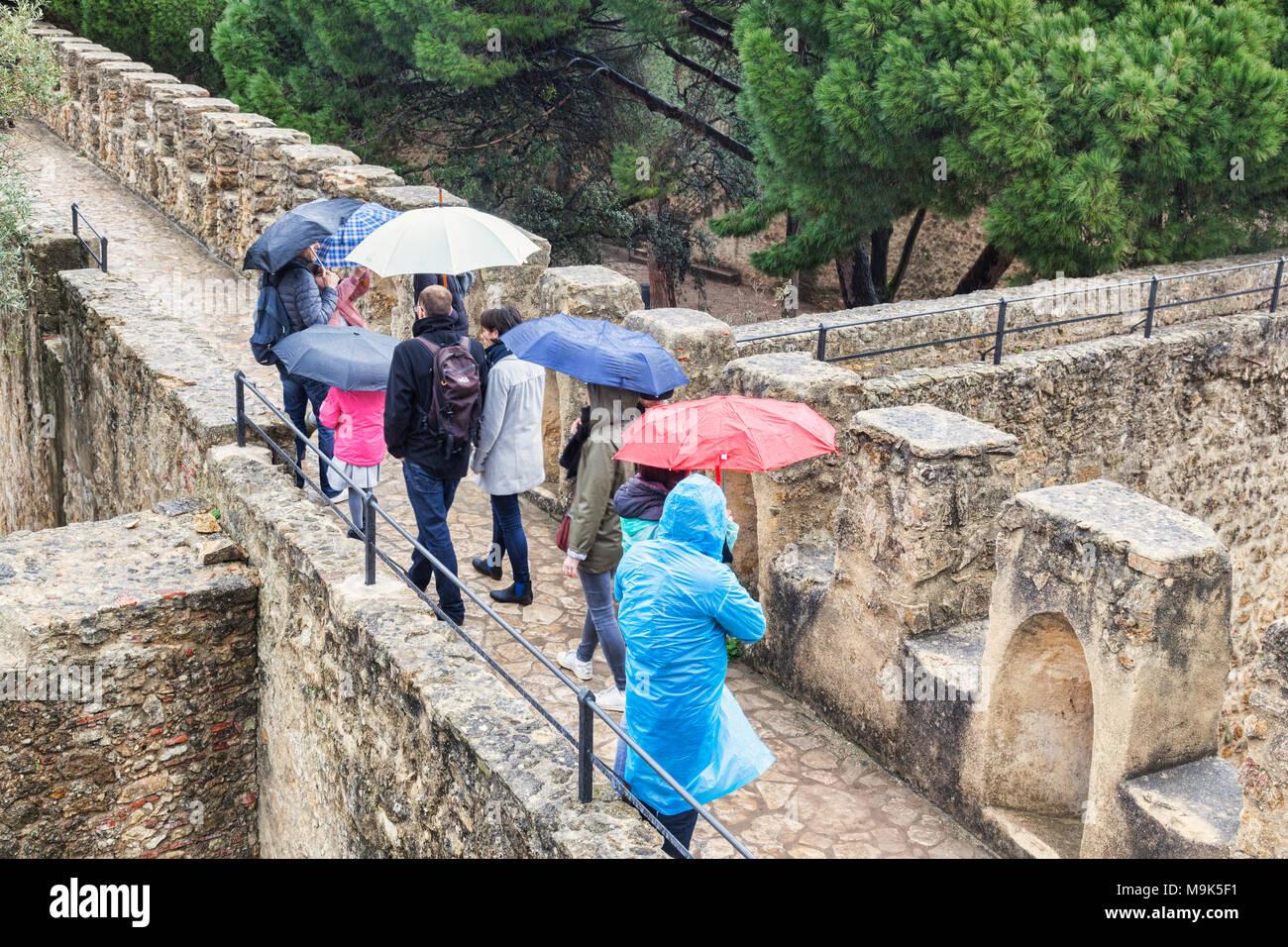 1 mars 2018: Lisbonne, Portugal - Les touristes avec des parasols sur les remparts de la Caste de Lisbonne, visite de la pluie. Photo Stock