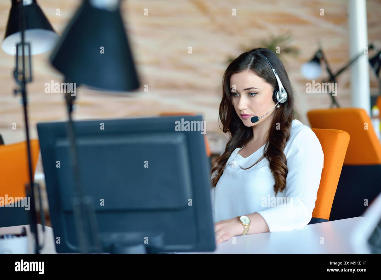 Jolie femme à écouter de la musique tout en travaillant dans le bureau d'affaires de démarrage Photo Stock