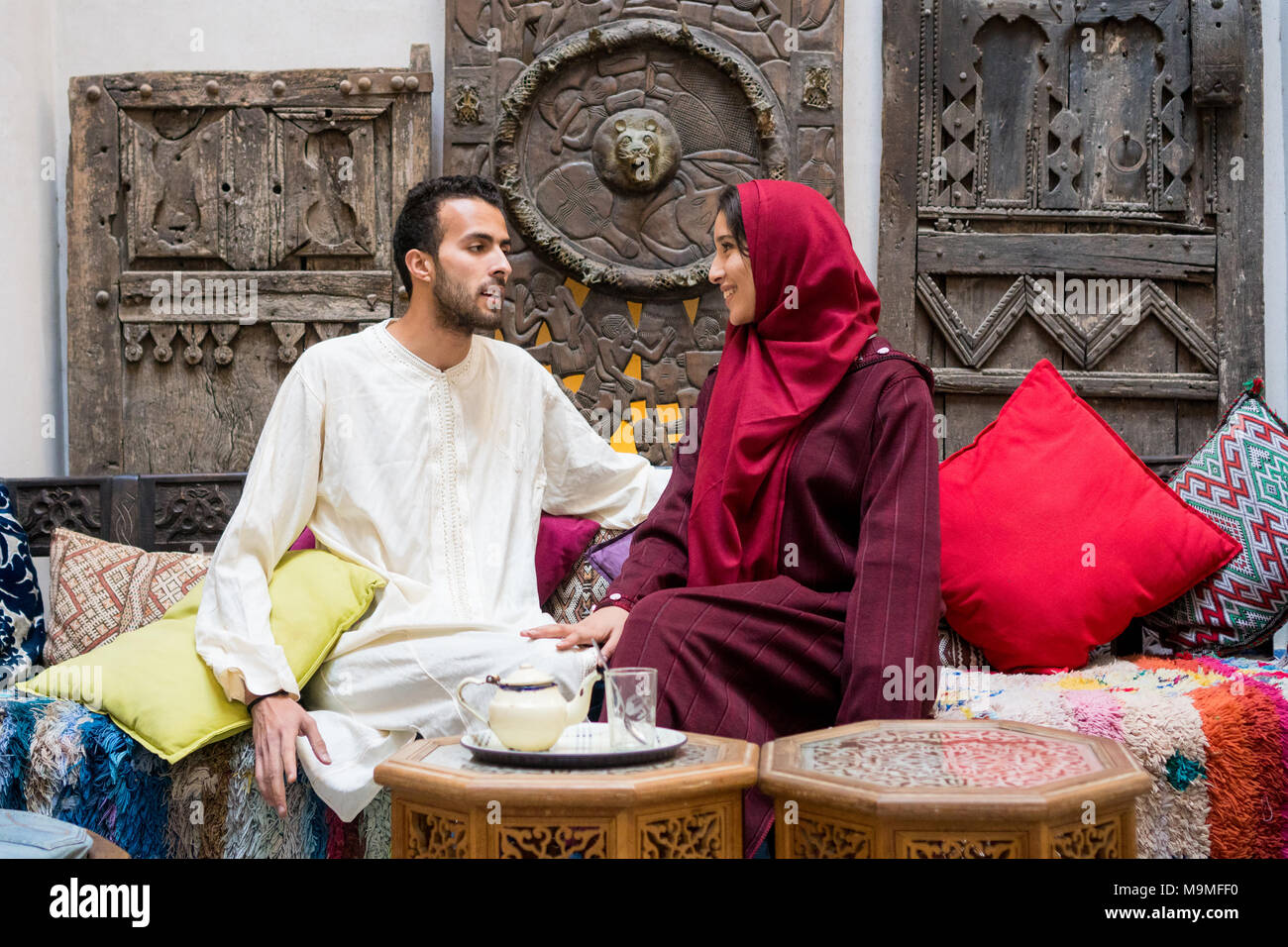 Couple jeune musulman en relation talking and smiling dans maison marocaine traditionnelle Photo Stock