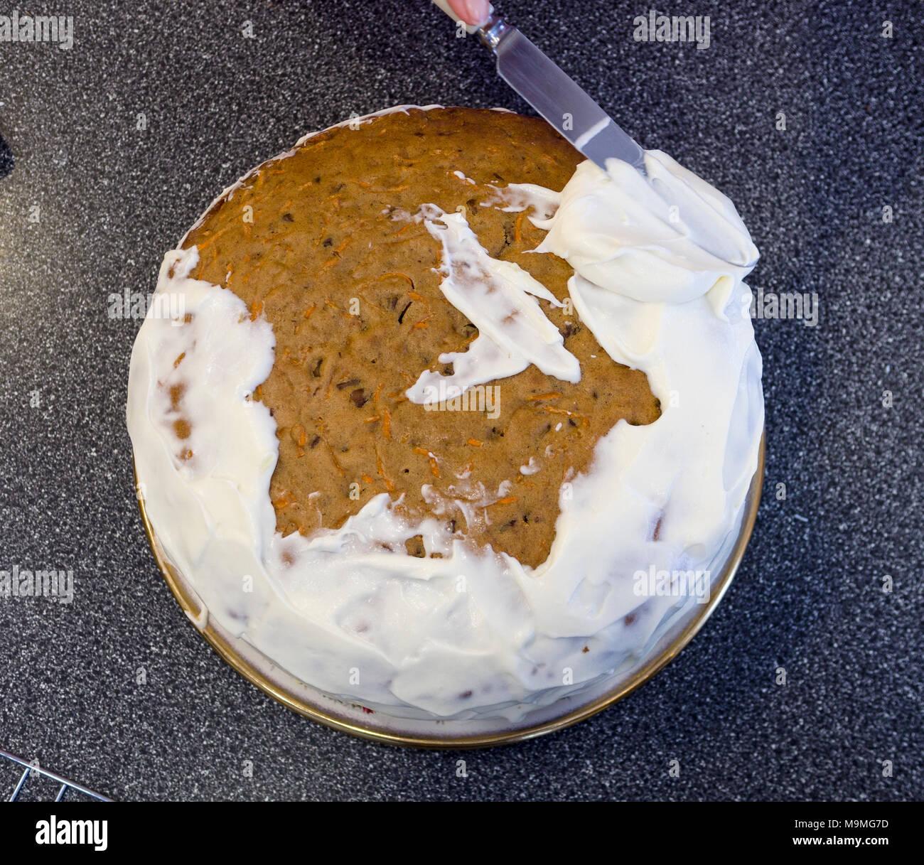 Glaçage et décoration d'un gâteau de carotte : étaler le glaçage blanc avec un couteau les premières étapes. Banque D'Images