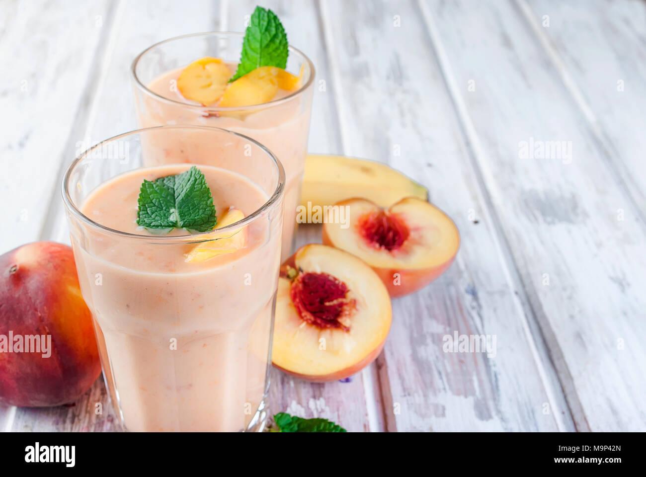 Smoothie d'été rafraîchissante ou milkshake avec abricot, pêche et la banane, menthe, yaourt en verre avec des ingrédients, sur table en bois blanc, copie Espace, haut Photo Stock