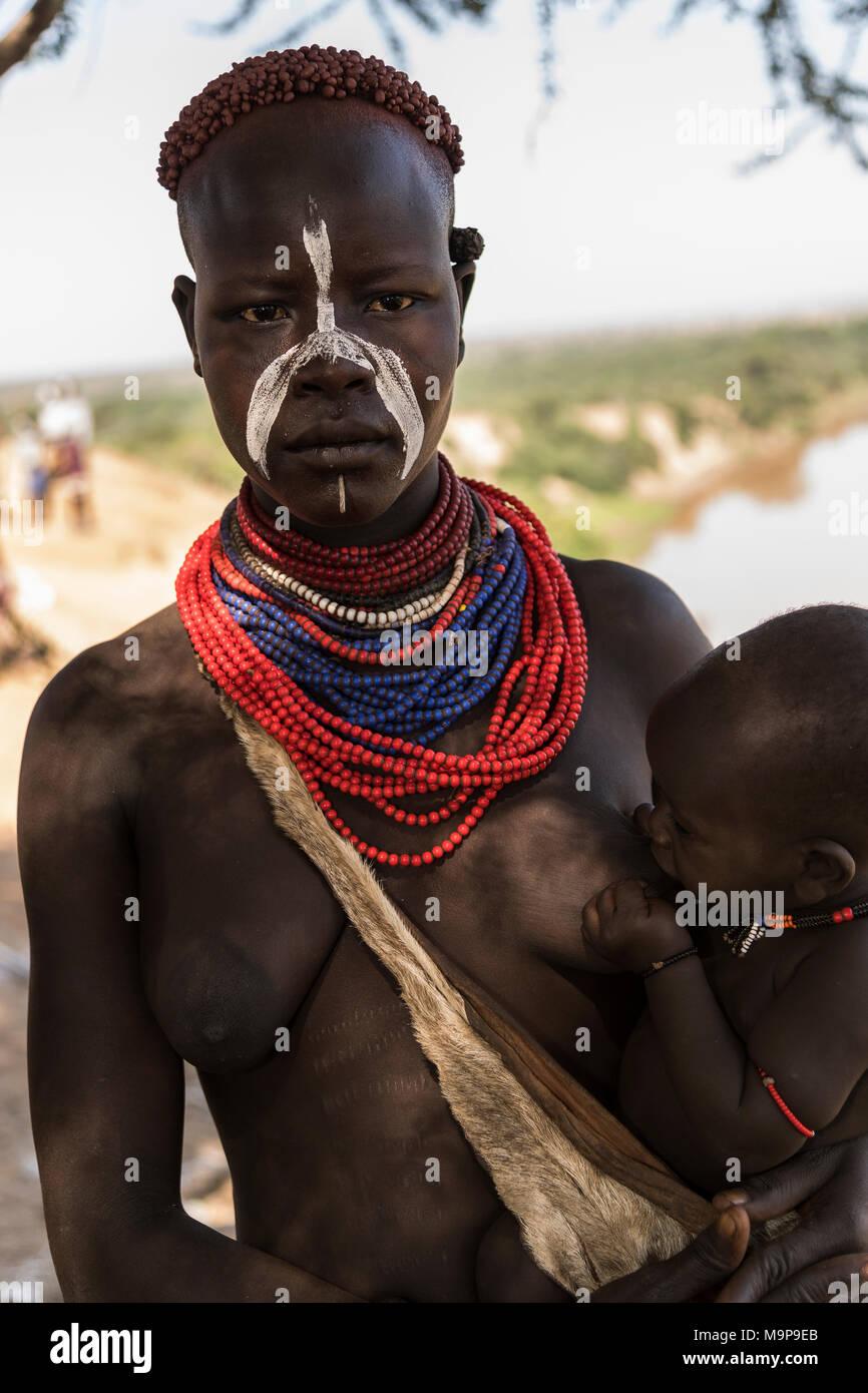 Jeune femme allaitait, tribu Karo, rivière Omo, Nationalités et Peuples du Sud, l'Éthiopie Région' Banque D'Images