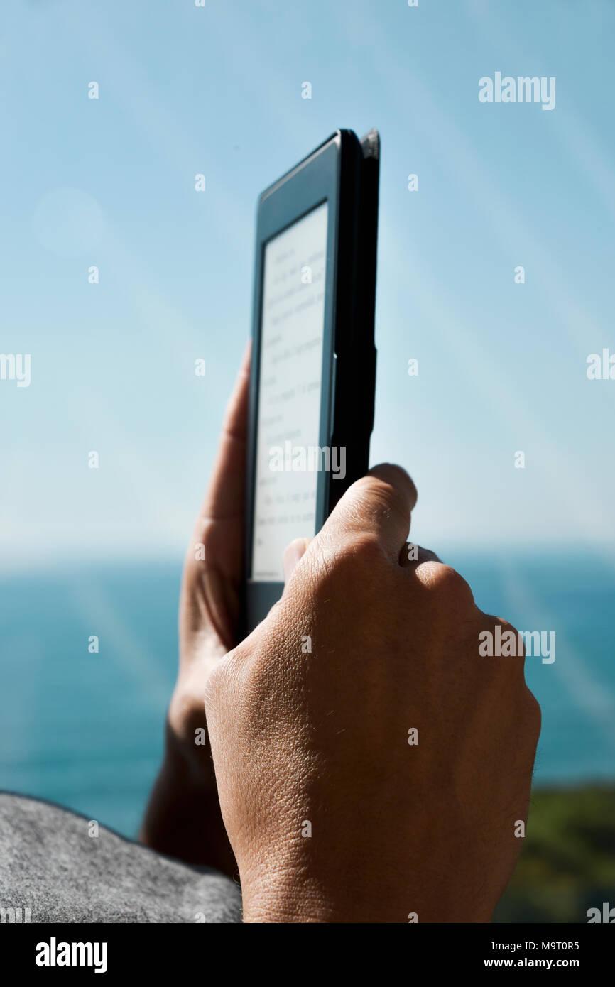 Libre d'un jeune homme de race blanche lecture à une tablette ou un e-reader à côté d'un balcon Photo Stock