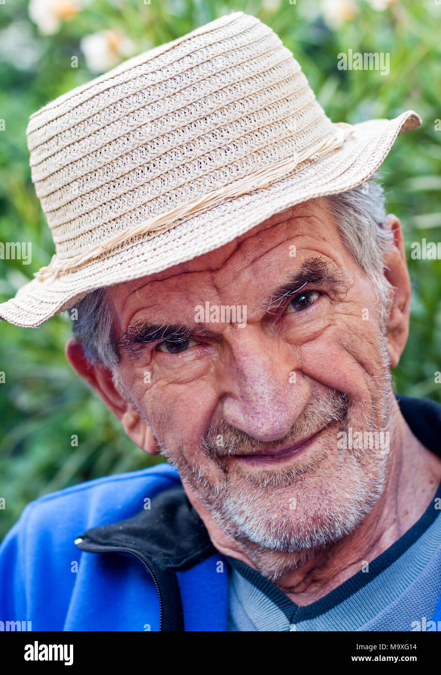 Un portrait d'un beau sourire, un homme âgé dans la région de hat à l'extérieur. Banque D'Images