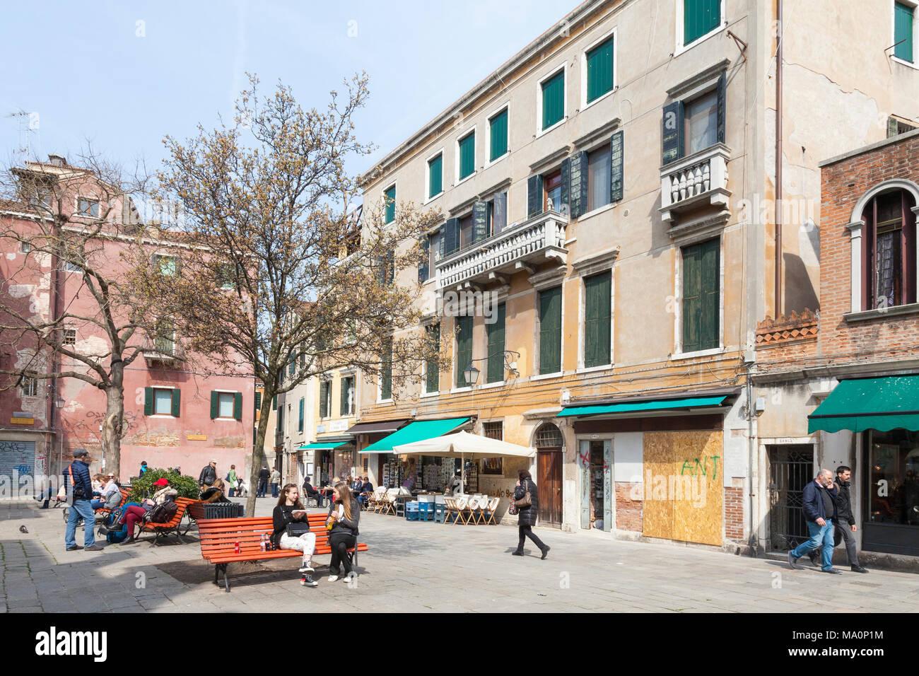 Campo Santa Maria Nova, Cannaregio, Venise, Vénétie, Italie avec les Vénitiens et les touristes assis sur des bancs profitant du soleil d'hiver Photo Stock