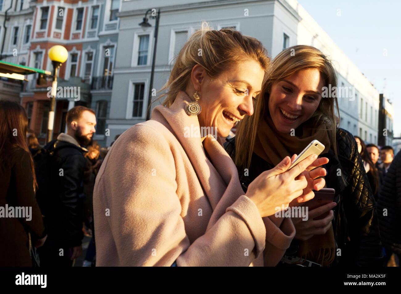Les jeunes adultes femelles smiling avec émotion, looking at mobile phone téléphone intelligent. La communication. La génération y exprimer ses émotions. Les amis et la famille. Photo Stock