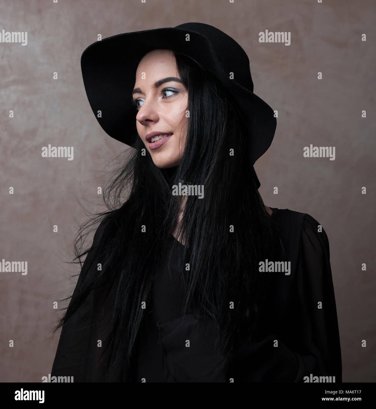 05d4be9a47856 Jolie jeune fille en chapeau noir et élégant haut noir a l'air mélancolique  -