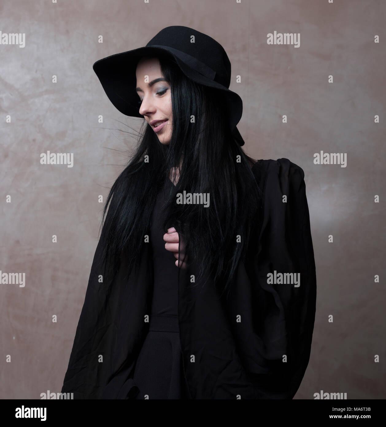 7ec2098d2e2d9 Jolie jeune fille en chapeau noir et élégant haut noir a l'air mélancolique  - tête et épaules - hobo fashion