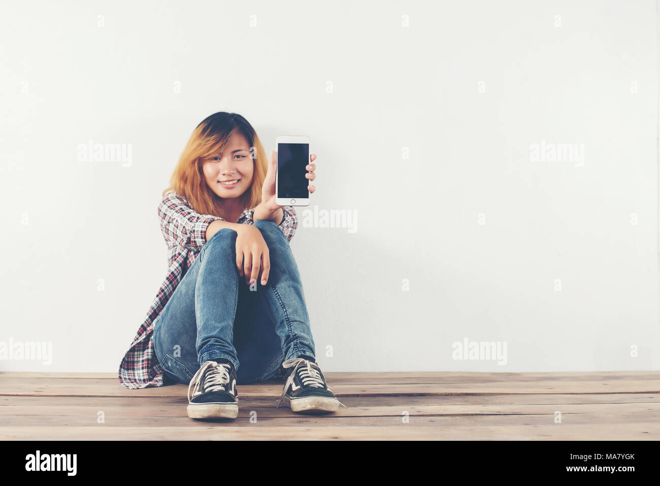 Heureux jeune hipster woman sitting on wooden floor holding smartphone à l'appareil photo. Photo Stock