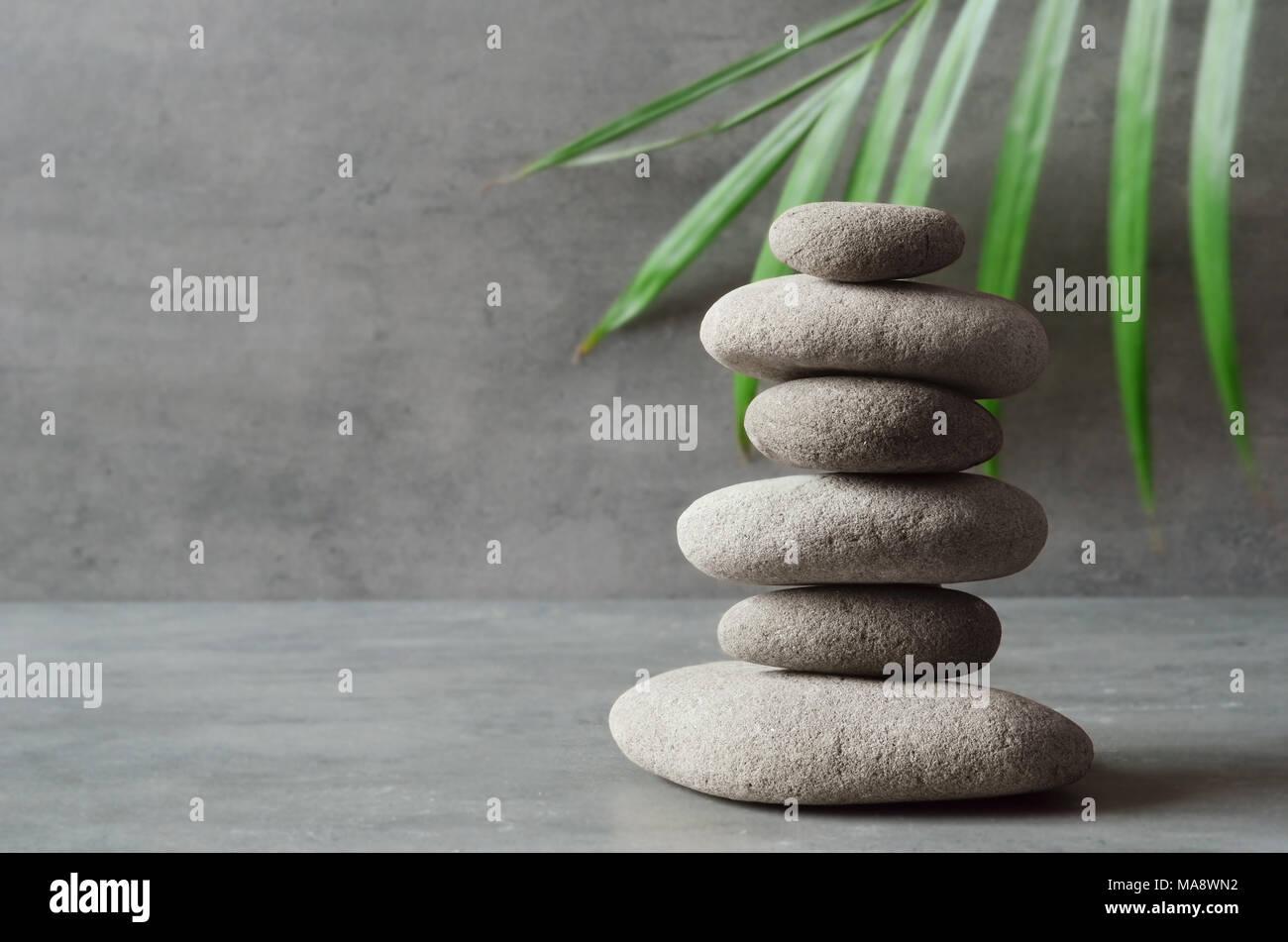 Des pierres et des feuilles de palmier vert l'équilibre. Concept spa et zen. Photo Stock