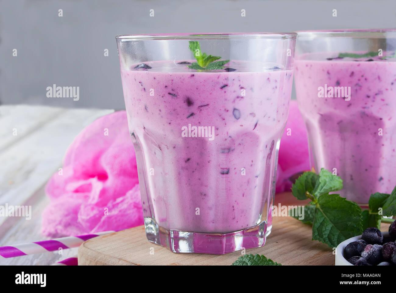 Violet d'été rafraîchissant smoothie ou milk-shake à la menthe, yaourt et myrtilles. dans le verre avec des ingrédients, sur table béton gris, copy space, haut Photo Stock