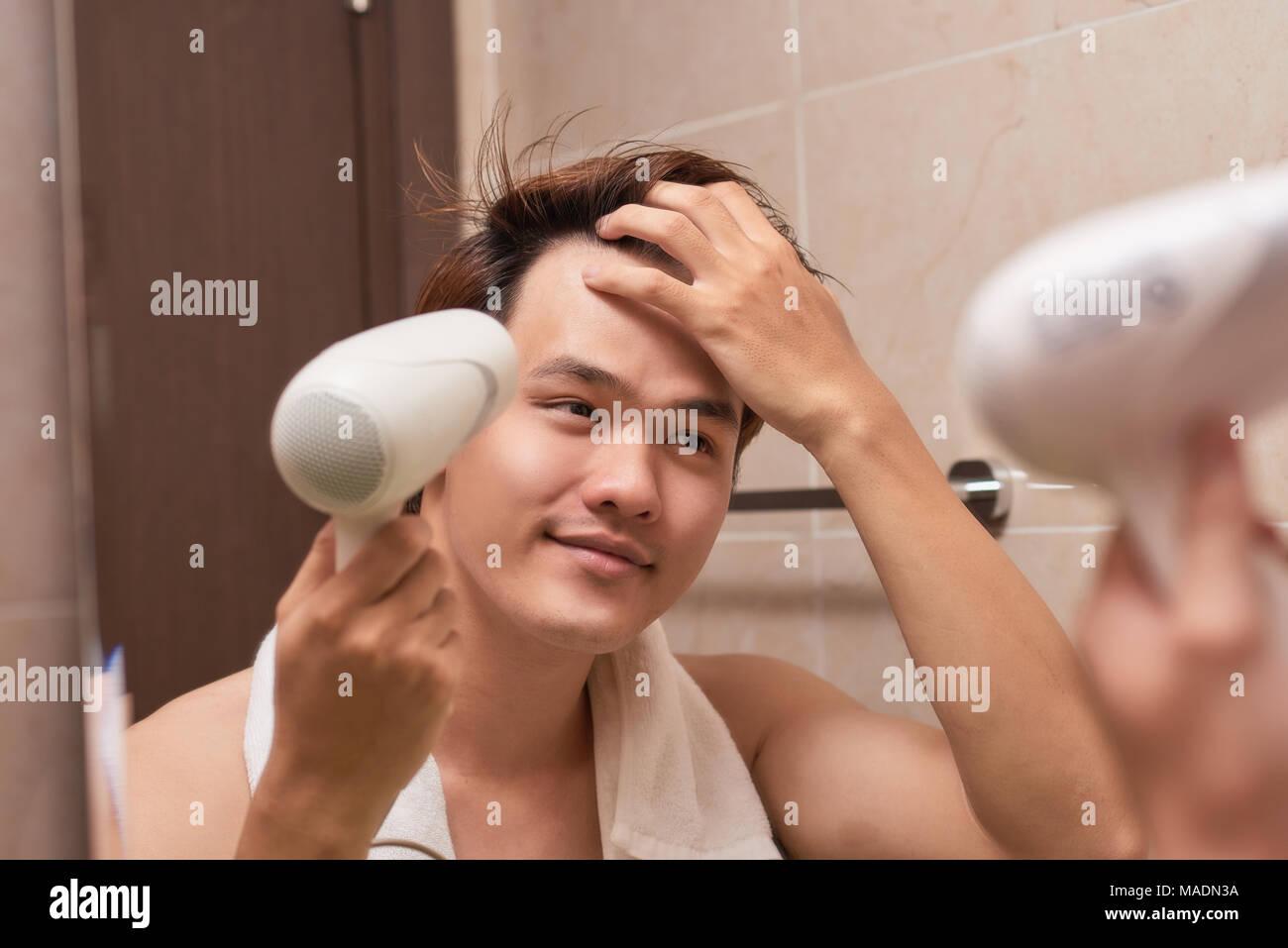Young Asian man blow drying hair dans salle de bains Photo Stock