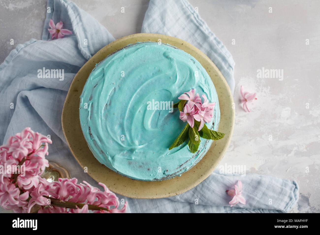 Élégant bleu gâteau avec des fleurs et de la menthe. Copier l'espace, vue d'en haut. Photo Stock