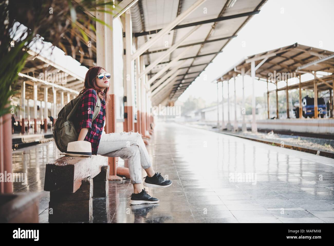d30c4ab629 Jeune femme avec sac à dos touristiques hipster assis dans la gare. Maison  de vacances concept touristique.