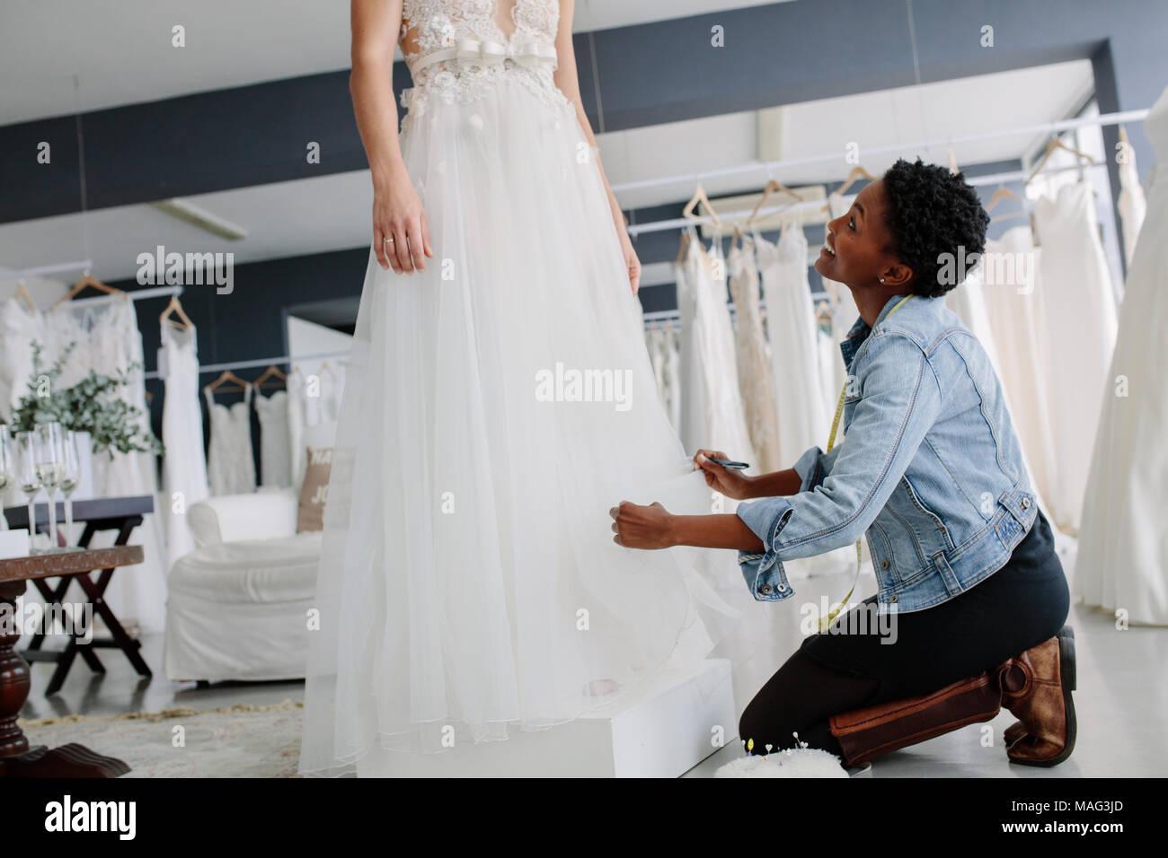 Femme d'effectuer le réglage à nuptiale de robe de mariage en fashion store. Dans sa robe de mariée avec robe femme designer de faire les ajustements nécessaires au toucher rectal Photo Stock